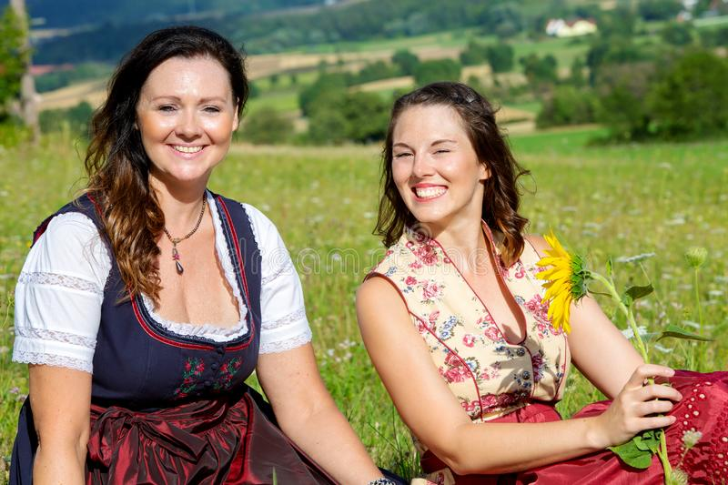 Two woman in dirndl sitting on blanket in meadow and laughing. Portrait of two women in dirndl sitting on blanket in meadow and laughing royalty free stock image