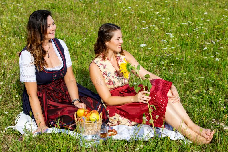 Two woman in dirndl sitting on blanket in meadow and smiling. Portrait of two women in dirndl sitting on blanket in meadow and smiling royalty free stock images