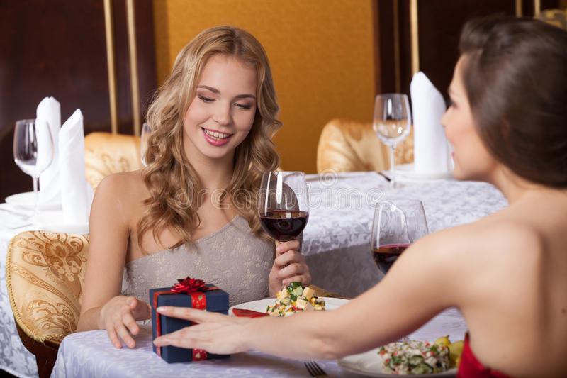 Two woman friends eating at restaurant and talking. stock image