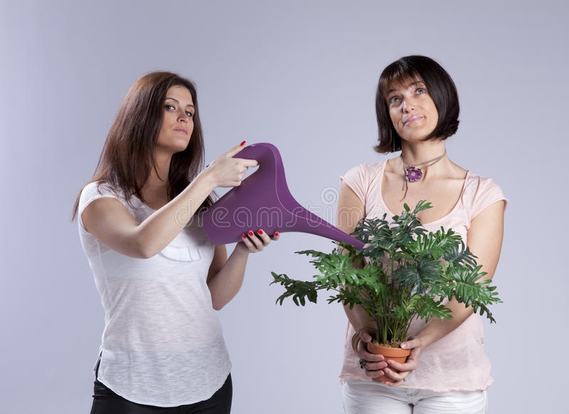 Two woman gardening. One woman holding a watering can and the other holding a plant royalty free stock images