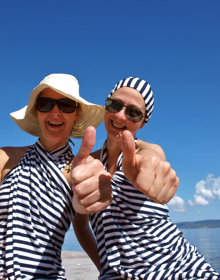 Two woman giving thumbs up royalty free stock image
