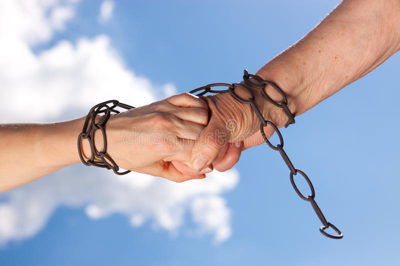 Two woman hands are chained together stock images
