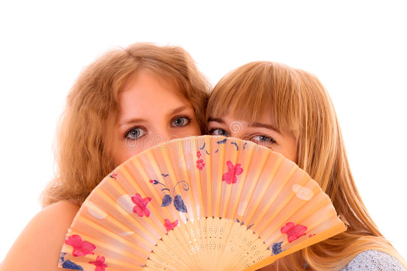 Two woman hiding with fan isolated