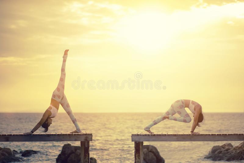 two woman playing yoga pose on wooden pier against sun rising over sea beach stock photography