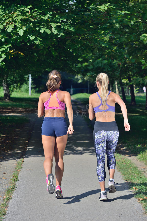 Two woman practicing working out - fitness outdoor at the park. Two women practicing working out - fitness outdoor at the park stock images