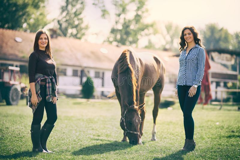 Two woman on ranch with horse. Two women on ranch with horse, outdoor in summer happy sunset nature stock images