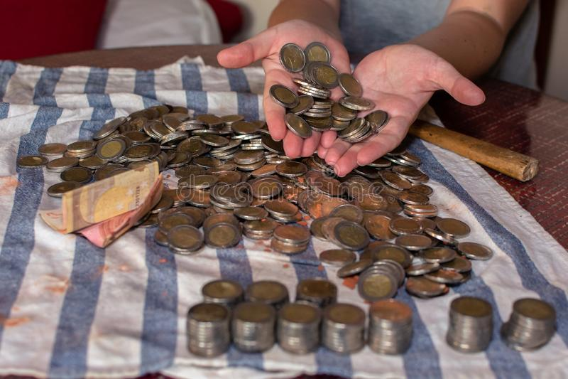 Two woman`s hands holding many coins and rows of stacked coins next to many coins scattered on a table royalty free stock photography