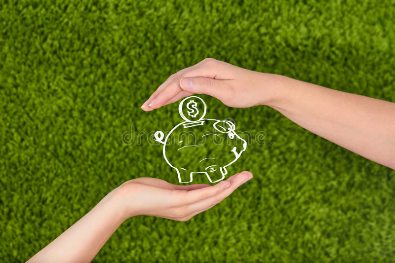 Two Woman's open hands making a protection gesture holding a piggy bank royalty free stock image