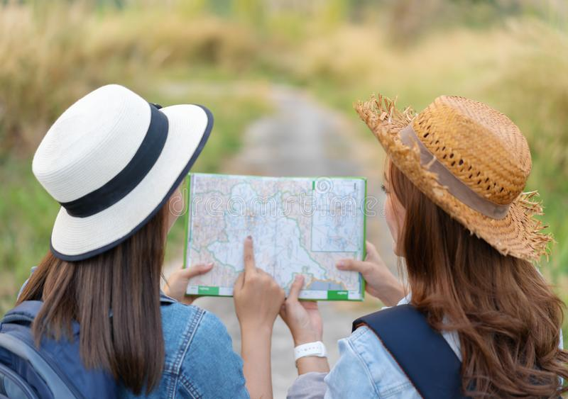 Two woman searching direction on location map while traveling. Two women traveler searching direction on location map while traveling stock photography
