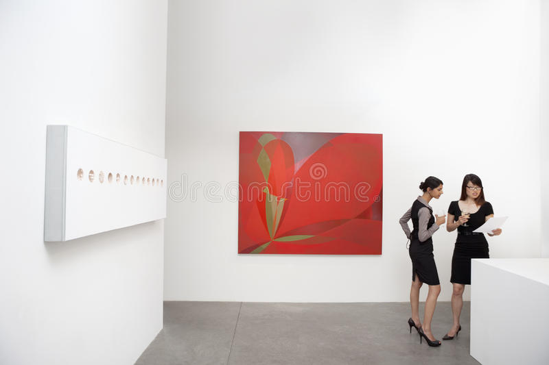 Two Woman Standing Next To Wall Paintings Stock Images
