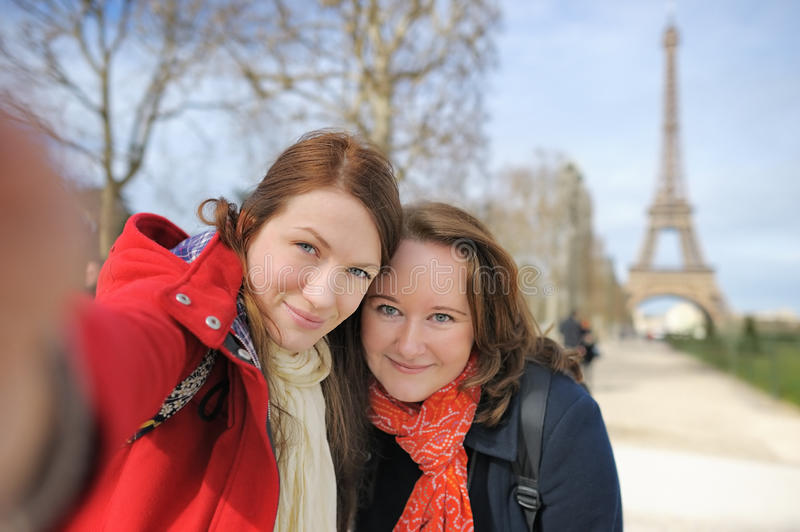 Two woman taking selfie near the Eiffel tower. Two young women taking a self portrait (selfie) near the Eiffel tower royalty free stock image