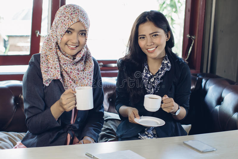 Two woman talking while enjoying coffee stock image