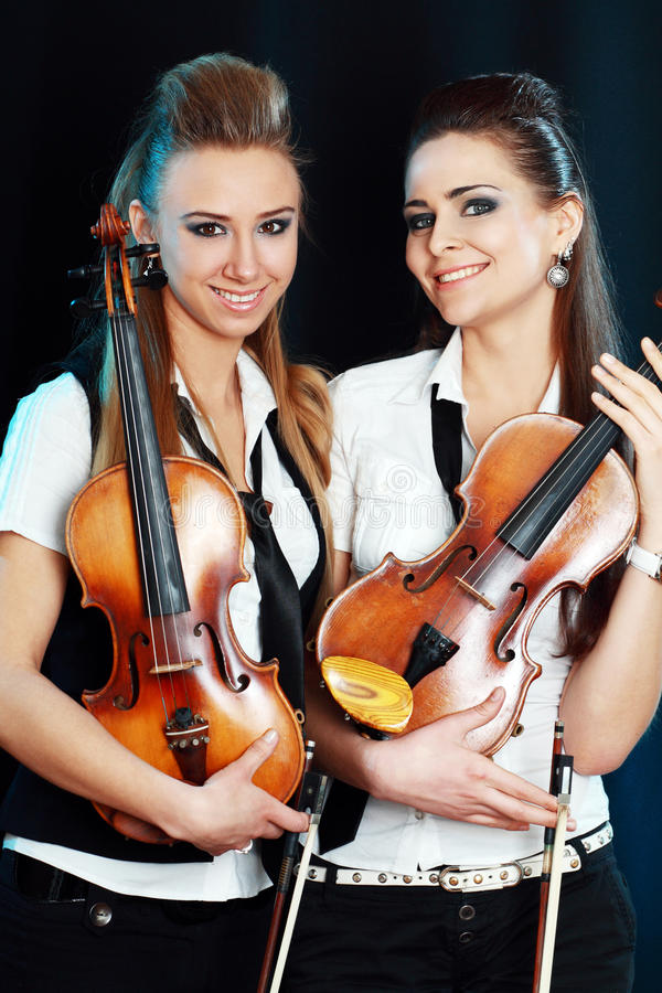 Two woman with violin. Two beautiful young women with violins over dark background royalty free stock photography