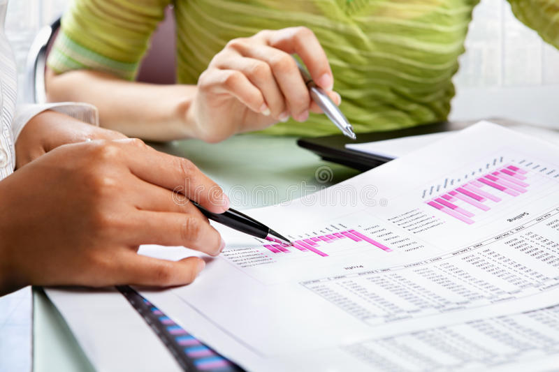 Two woman working on statistic stock image
