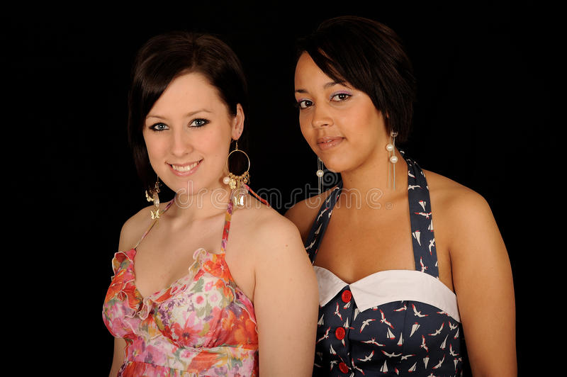 Two women. Wearing sleeveless dresses. Isolated against a black background royalty free stock photos