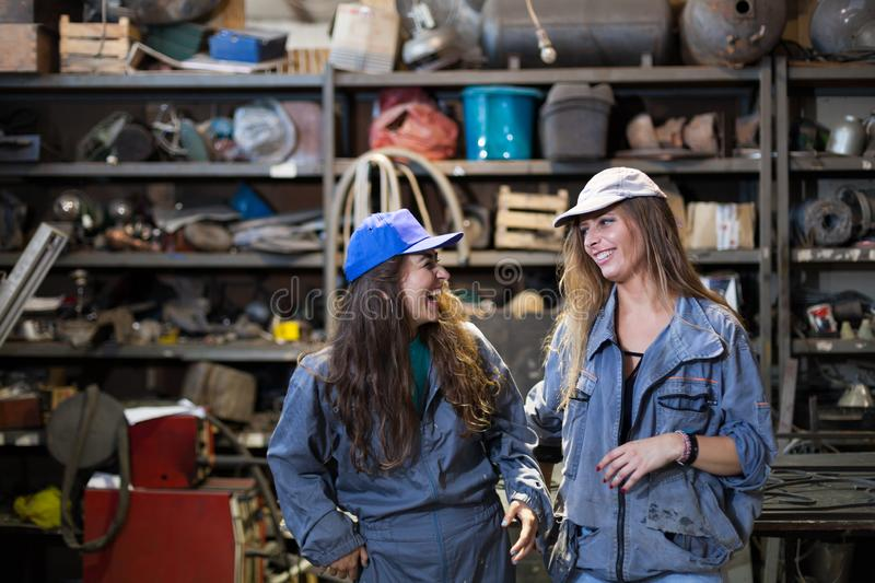 two women apprentices in a workshop stock photo