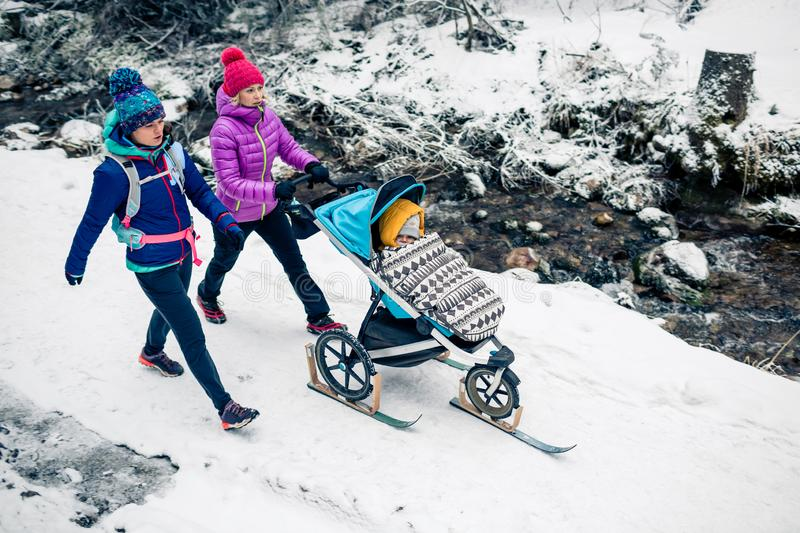 Two women with baby stroller enjoying winter in forest, family time royalty free stock image