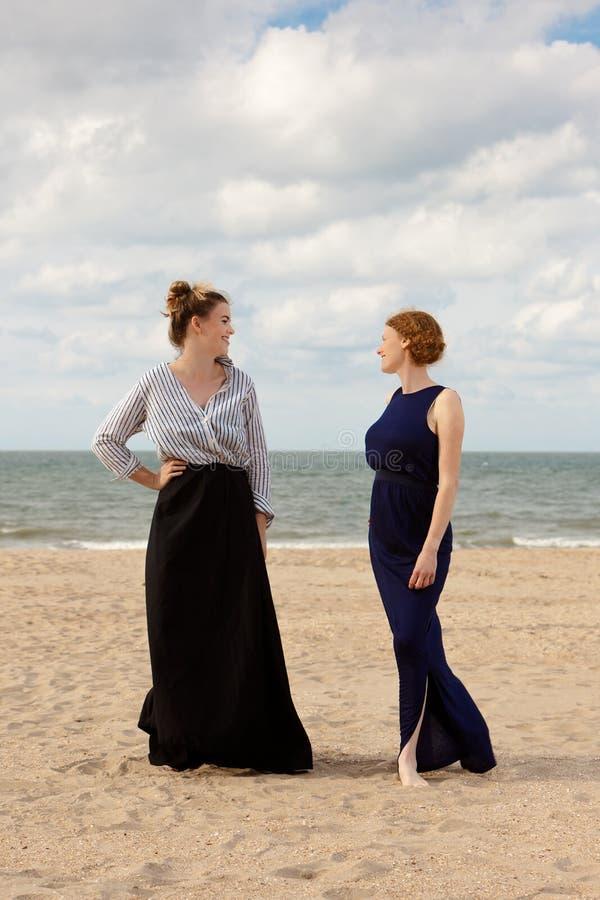 Two women beach sand sea talking, De Panne, Belgium. Two women in retro dresses talking on the beach at the sea in De Panne, Belgium royalty free stock photo