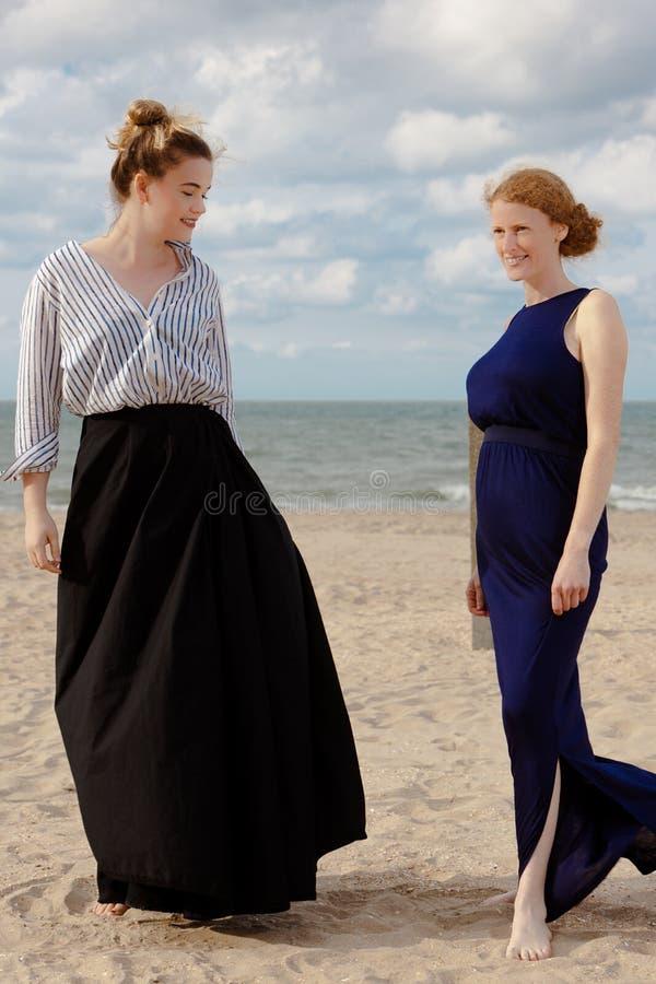 Two women beach sand sea talking, De Panne, Belgium. Two women in retro dresses talking on the beach at the sea in De Panne, Belgium stock images