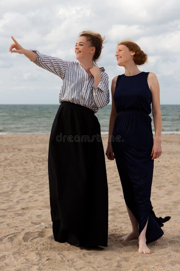 Two women beach sand sea talking, De Panne, Belgium. Two women in retro dresses talking on the beach at the sea in De Panne, Belgium royalty free stock photography
