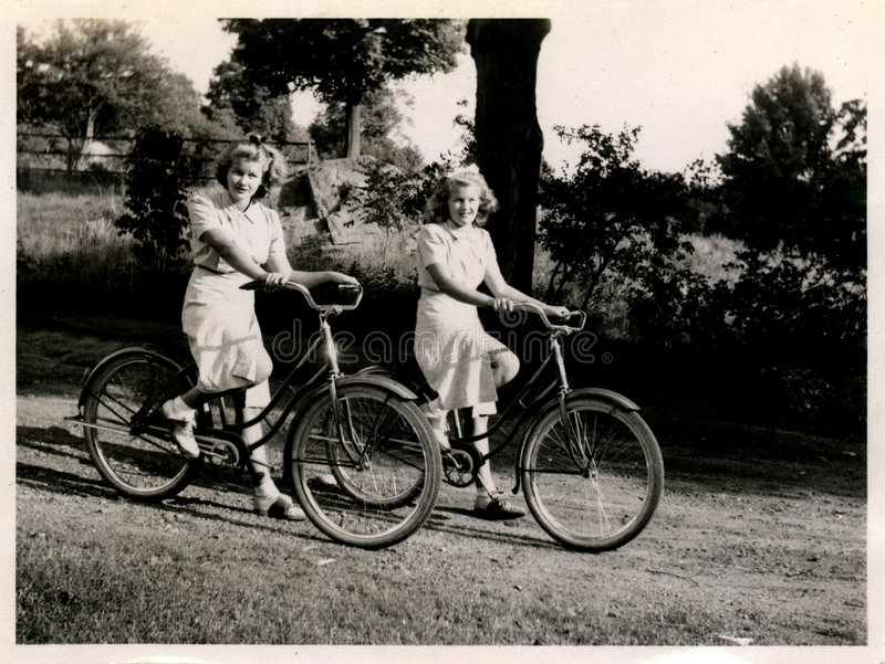 Two women on bicycles stock image