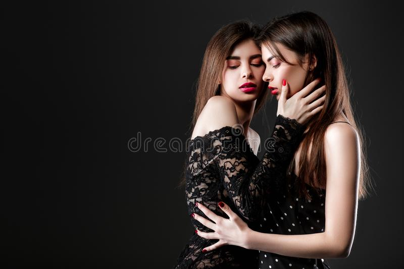 Two women in a black dress. Twins royalty free stock photo