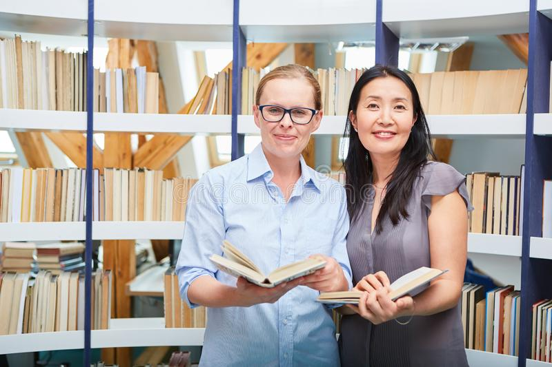 Two women with book as a reader in the library. Two young women with book as a reader or self-confident librarians in the library stock photo
