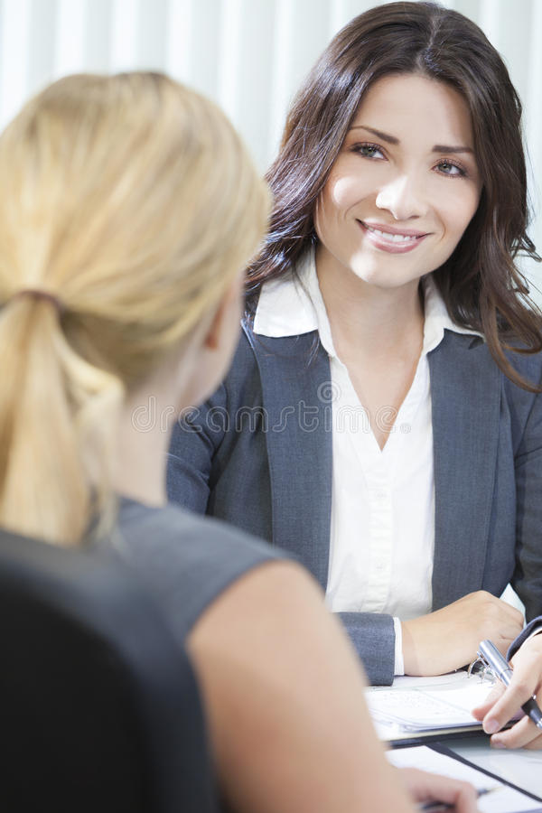 Two Women or Businesswomen in Office Meeting. Two young women executives or businesswomen in smart business suits sitting at a desk in an office having a meeting stock photography