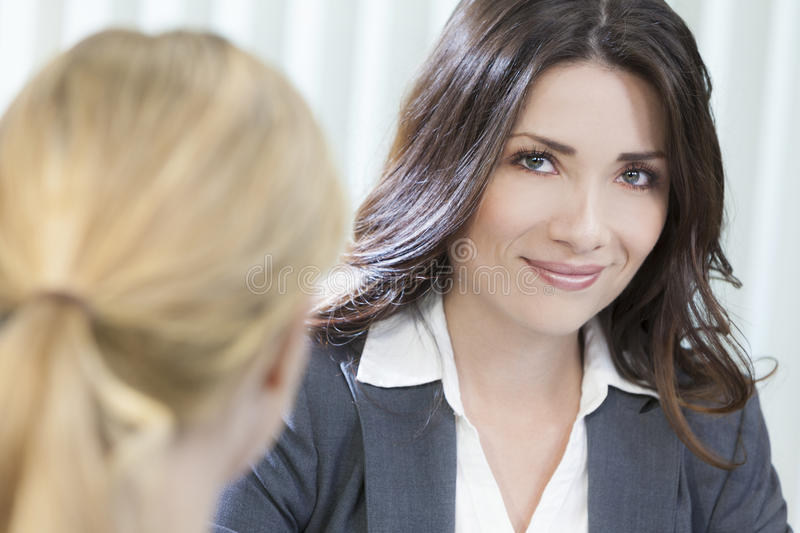 Two Women or Businesswomen in Office Meeting. Two young women executives or businesswomen in smart business suits sitting at a desk in an office having a meeting royalty free stock photography