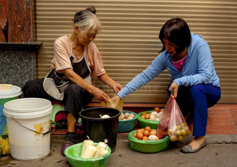 Two women buying and selling fresh eggs in the Old Quarter of Hanoi, Vietnam. Two local women selling fresh meat on the street in the Old Quarter of Hanoi royalty free stock image