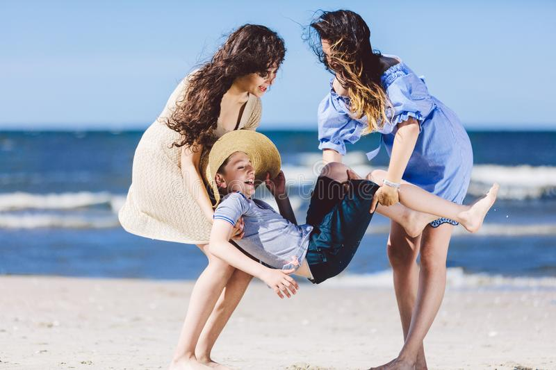 Two women carrying a boy in a straw hat on the beach. stock photo