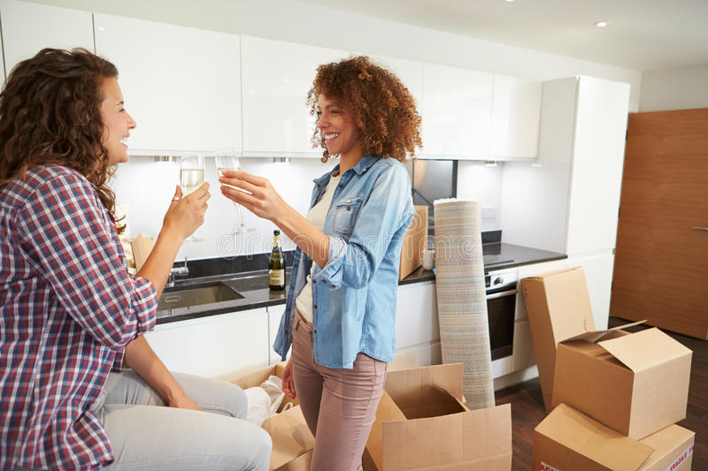 Two Women Celebrating Moving Into New Home With Champagne. Looking At Each Other Smiling stock photography
