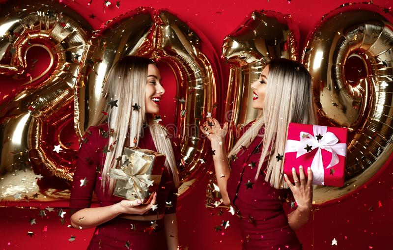 Two women celebrating at new year party happy laughing girls in casual dresses throw gold stars confetti with 2019 balloons. Two women celebrating at new year stock photo