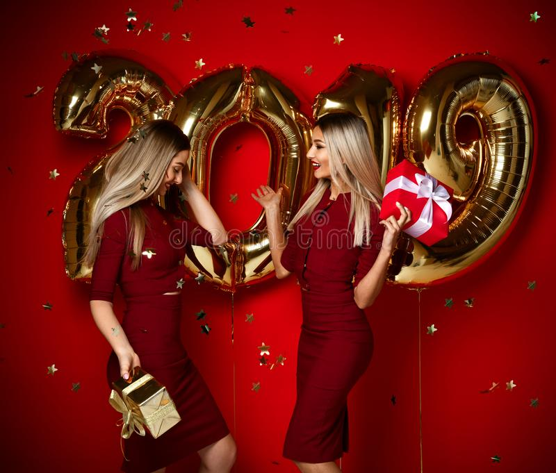 Two women celebrating at new year party happy laughing girls in casual dresses throw gold stars confetti with 2019 balloons. Two women celebrating at new year stock photos