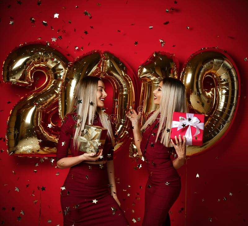 Two women celebrating at new year party happy laughing girls in casual dresses throw gold stars confetti with 2019 balloons. Two women celebrating at new year stock images