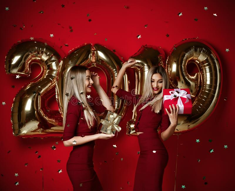 Two women celebrating at new year party happy laughing girls in casual dresses throw gold stars confetti with 2019 balloons. Two women celebrating at new year stock photography