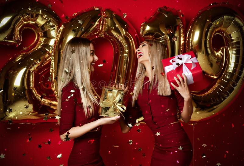 Two women celebrating at new year party happy laughing girls in casual dresses throw gold stars confetti with 2019 balloons. Two women celebrating at new year stock image