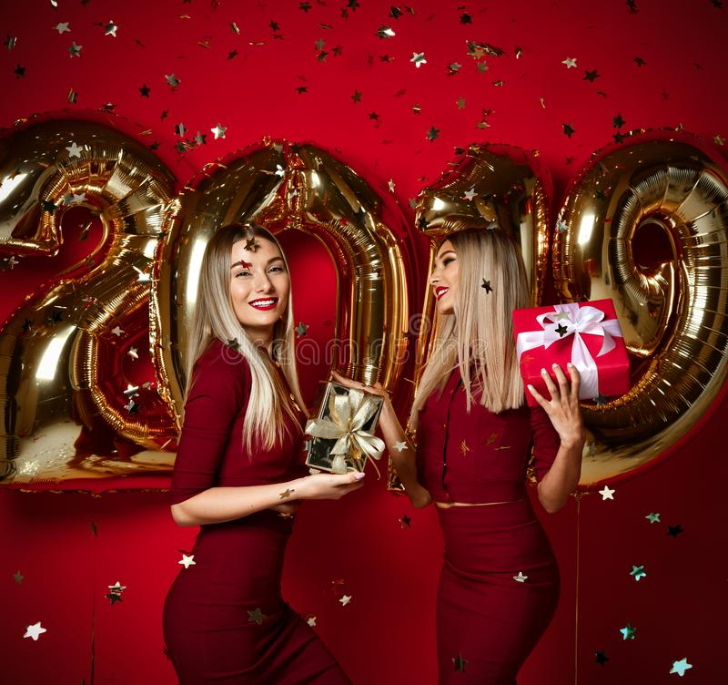 Two women celebrating at new year party happy laughing girls in casual dresses throw gold stars confetti with 2019 balloons. Two women celebrating at new year royalty free stock photography