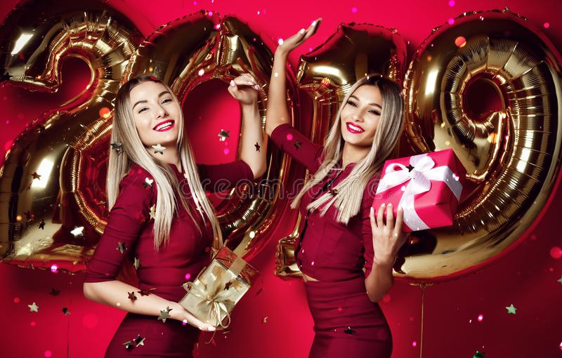Two women celebrating at new year party happy laughing girls in casual dresses throw gold stars confetti with 2019 balloons. Two women celebrating at new year royalty free stock photo