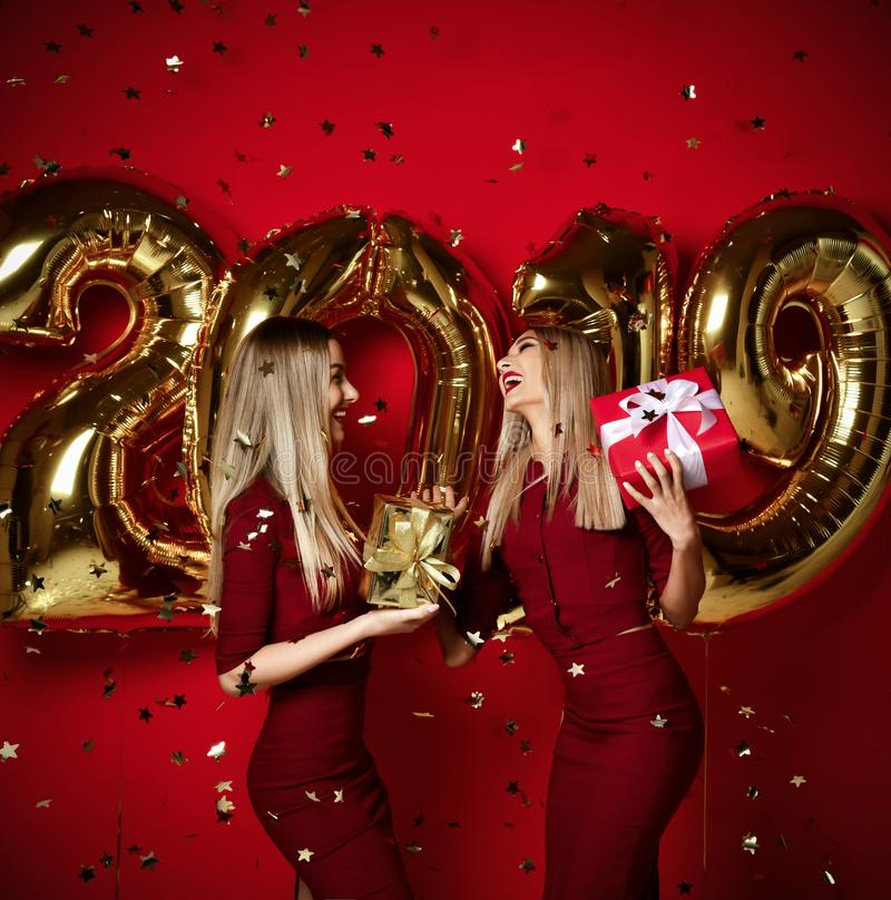 Two women celebrating at new year party happy laughing girls in casual dresses throw gold stars confetti with 2019 balloons. Two women celebrating at new year royalty free stock photos