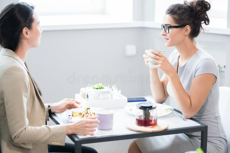Two Women Chatting at Cafe Table stock images