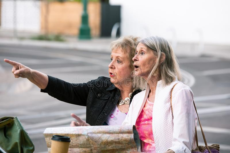 Two Women Checking Directions on a roadmap. Two smiling women in a city center with a road map at their car royalty free stock photos