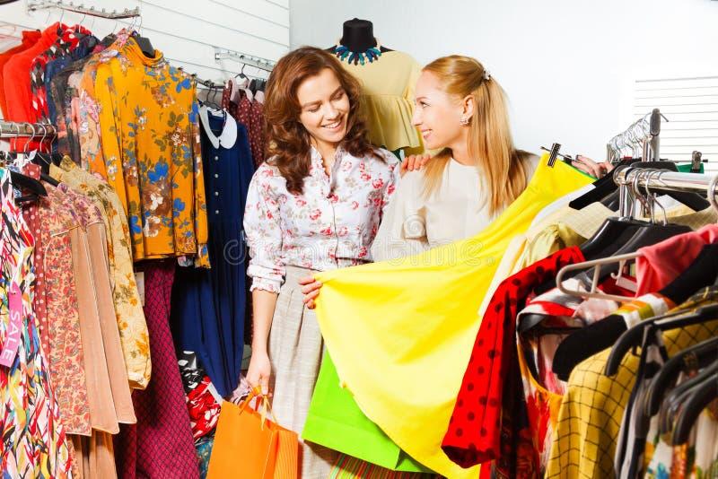 Two women choosing yellow skirt in shop royalty free stock photos