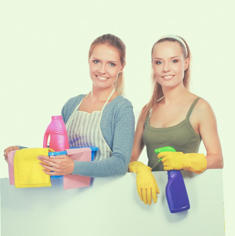 Two women is cleaning something with wisp and spray attentively. Two women is cleaning something with wisp and spray attentively royalty free stock photo