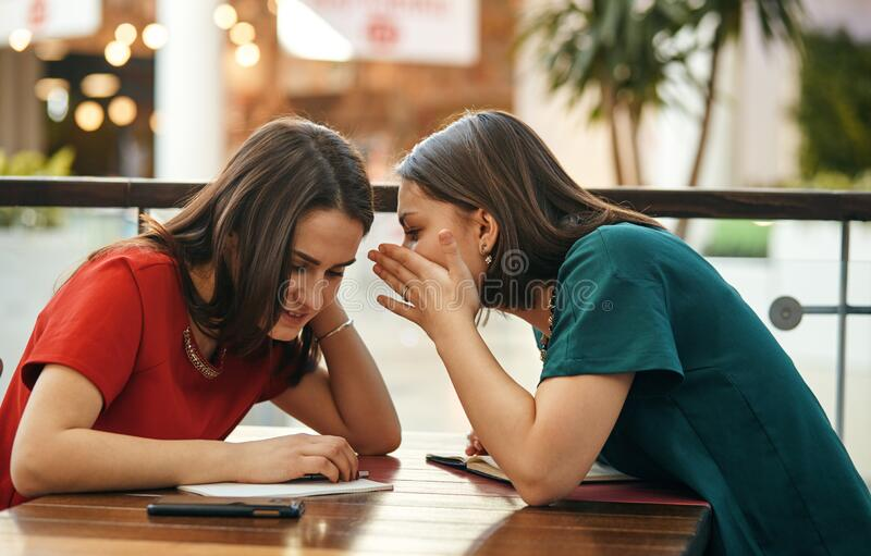 Two women communicate sitting at the table stock photography