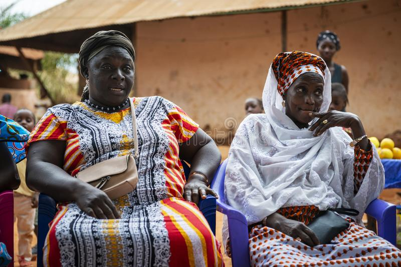 Two women at a community meeting at the Missira neighborhood in the city of Bissau. Bissau, Republic of Guinea-Bissau - February 6, 2018: Two women at a stock photos