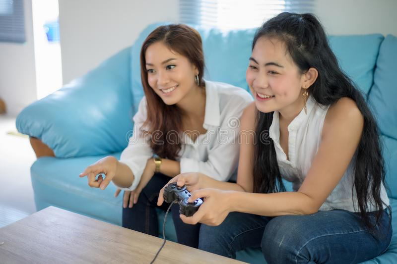 Two women Competitive friends playing video games and excited ha. Ppy cheerful at home royalty free stock image