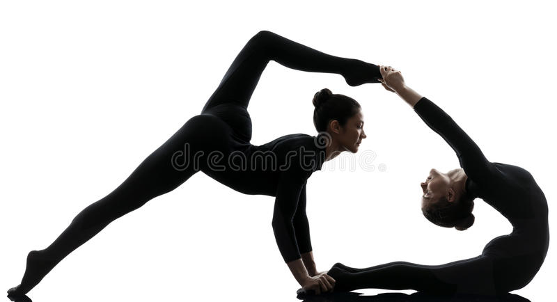 Two women contortionist exercising gymnastic yoga. Two women contortionist practicing gymnastic yoga in silhouette on white background