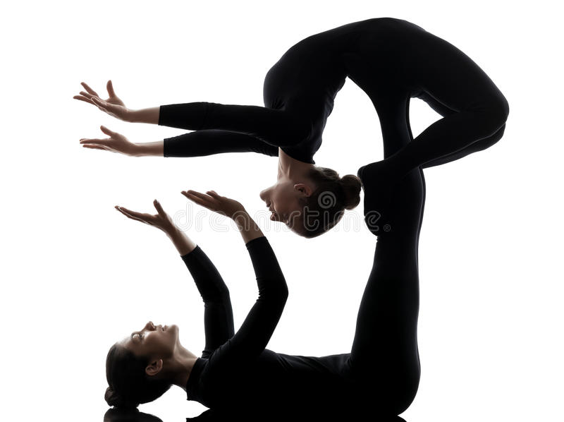 Two women contortionist exercising gymnastic yoga silhouette royalty free stock images