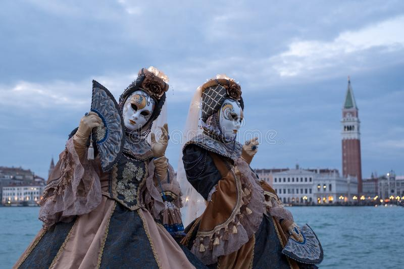 Two women in costumes and masks, with decorated fans, at San Giorgio, with St Marks Square and bell tower behind stock image